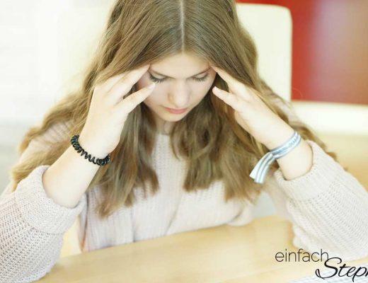 Kopfschmerzen bei Jugendlichen besser behandeln. Mädchen massiert sich die Schläfen