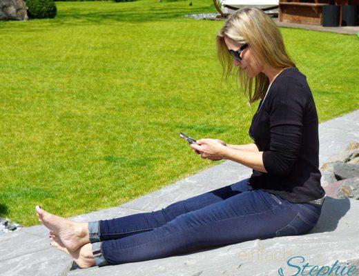 Stephie mit Smartphone im Garten