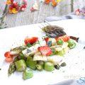 Spargelsalat mit Erdbeeren. Auf Teller angerichtet mit Gabel