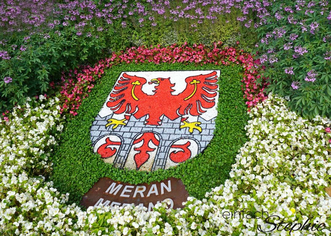 5 Tipps für Meran. Spaziergang durch Meran. Stadtwappen aus Blumen arrangiert
